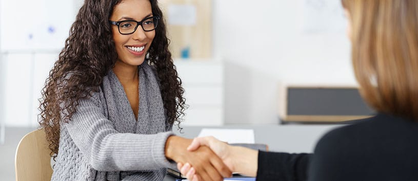 Two women shaking hands in an office.