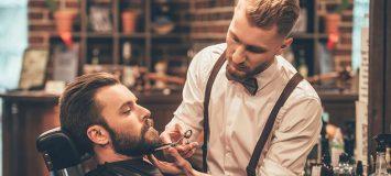 Man receiving beard trim in barber shop
