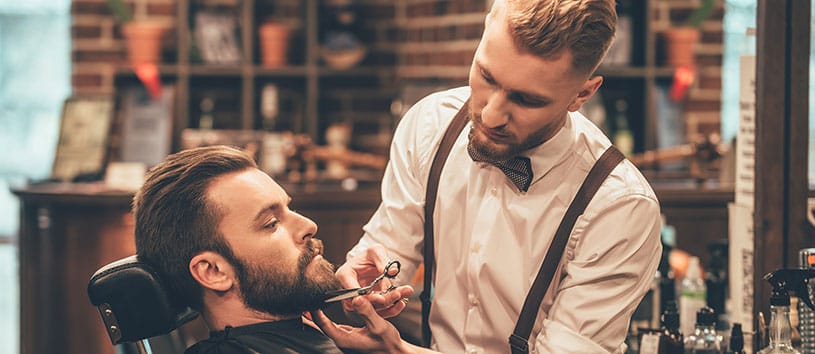 Man receiving beard trim in barber shop