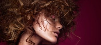 Side profile of woman with curly hair and bright makeup.