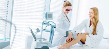 Woman receiving electrolysis treatment on her legs.