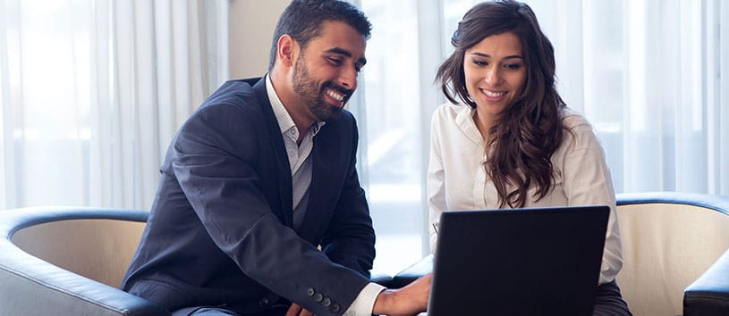 Man and woman smiling while looking at a laptop.