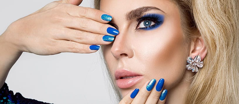 Woman with blue fingernails and blue eyeshadow.
