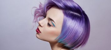 Side profile of a woman with short, purple/blue hair.