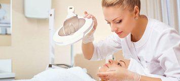 Esthetician examining a woman's skin.