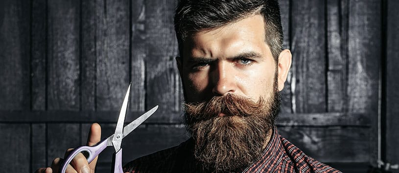 Bearded man holding scissors near his face.