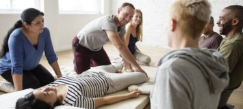 A class of aspiring massage therapists learning from their teacher
