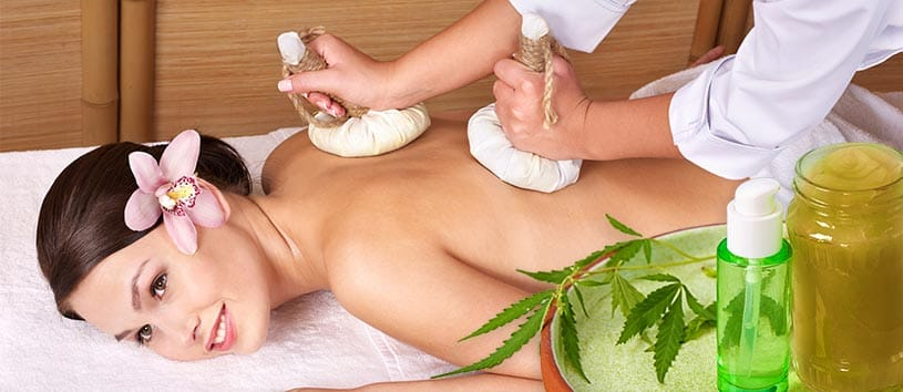 A woman receiving a massage with cannabis leaves and cream on the lower right hand corner
