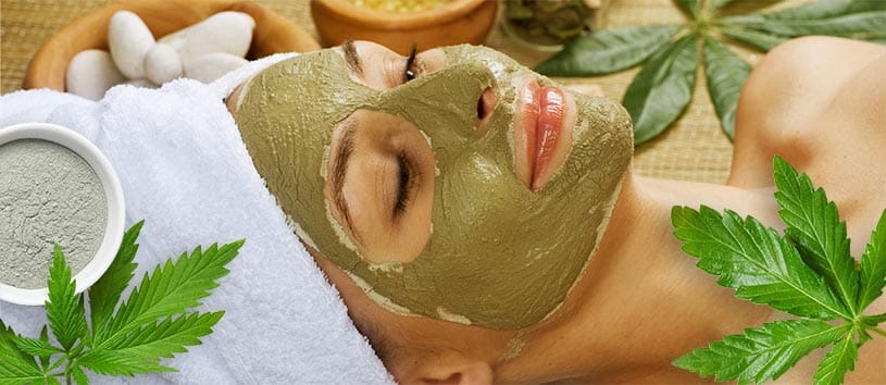 A woman with a green mud mask relaxing with hemp leaves overlaid